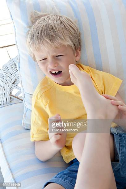 boy kicking his twin brother - male feet on face stock photos and pictures