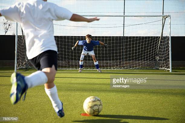 Boy (9-11) kicking soccer ball at goal, rear view