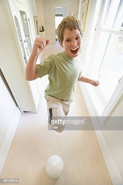 Boy Kicking Soccer Ball in Hallway