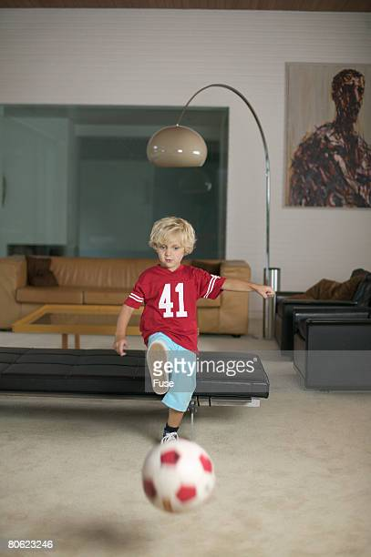 boy kicking soccer ball in living room - kicking stock pictures, royalty-free photos & images