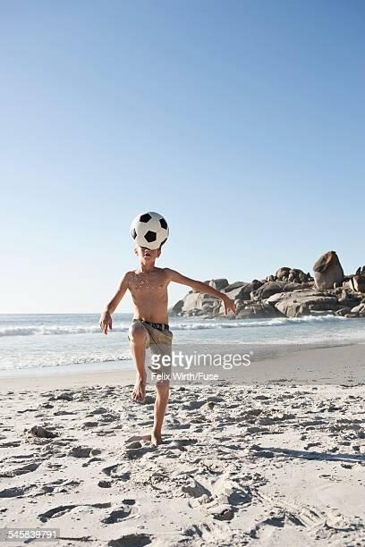 Boy (10-12) kicking soccer ball on beach