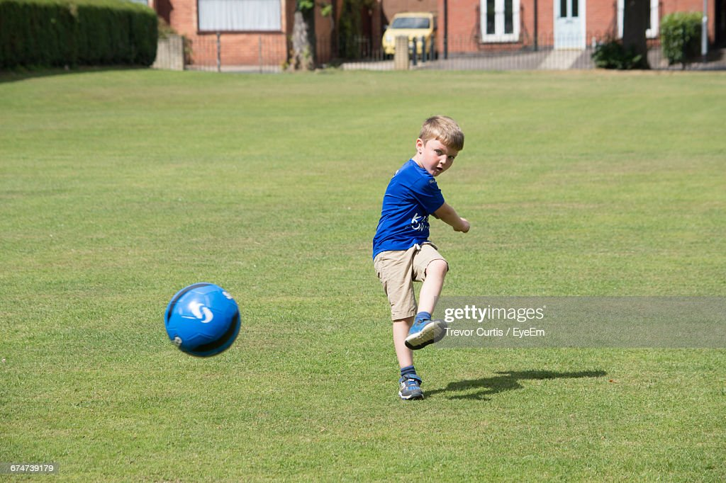 boy kicking soccer ball on grassy field stock photo getty images