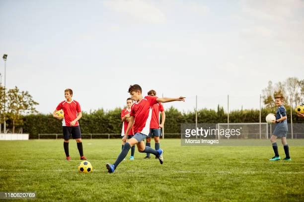 jongen schoppen soccer ball op de grond tijdens de training - voetbal stockfoto's en -beelden