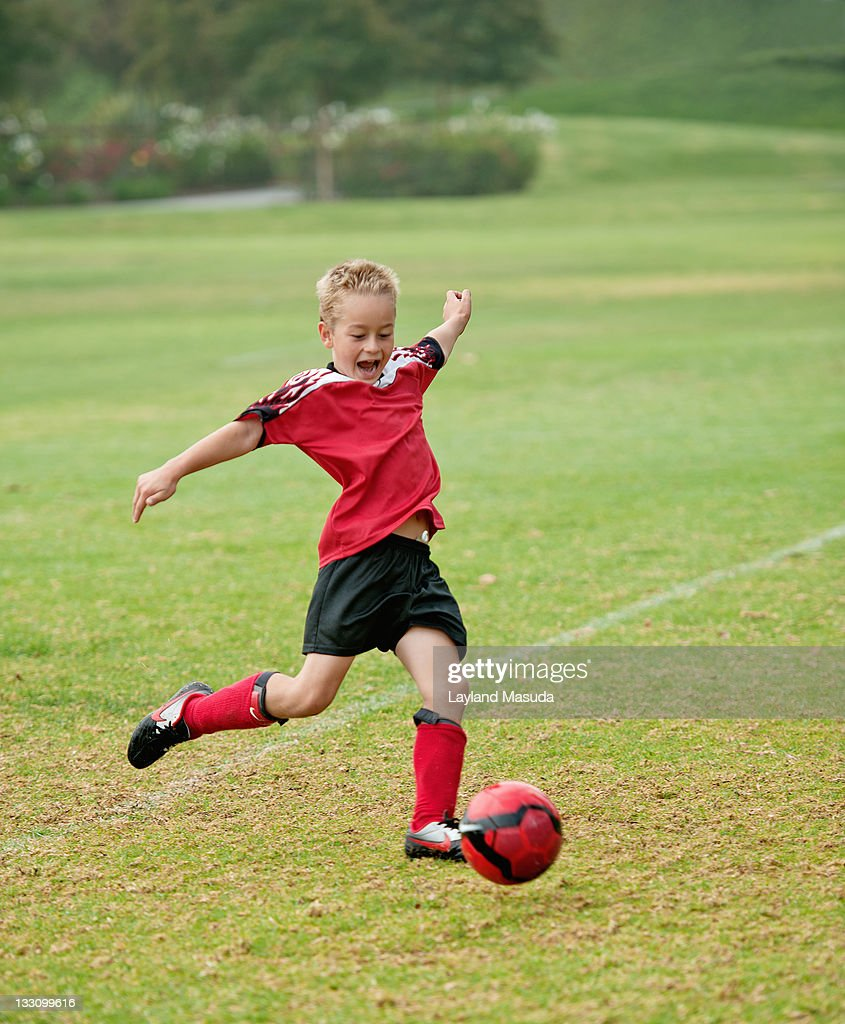 boy kicking soccer ball stock photo getty images