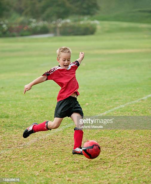 boy kicking soccer ball - kicking stock pictures, royalty-free photos & images