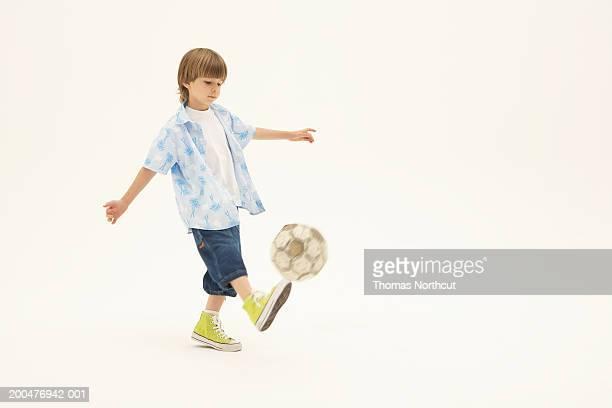 Boy (6-8) kicking soccer ball