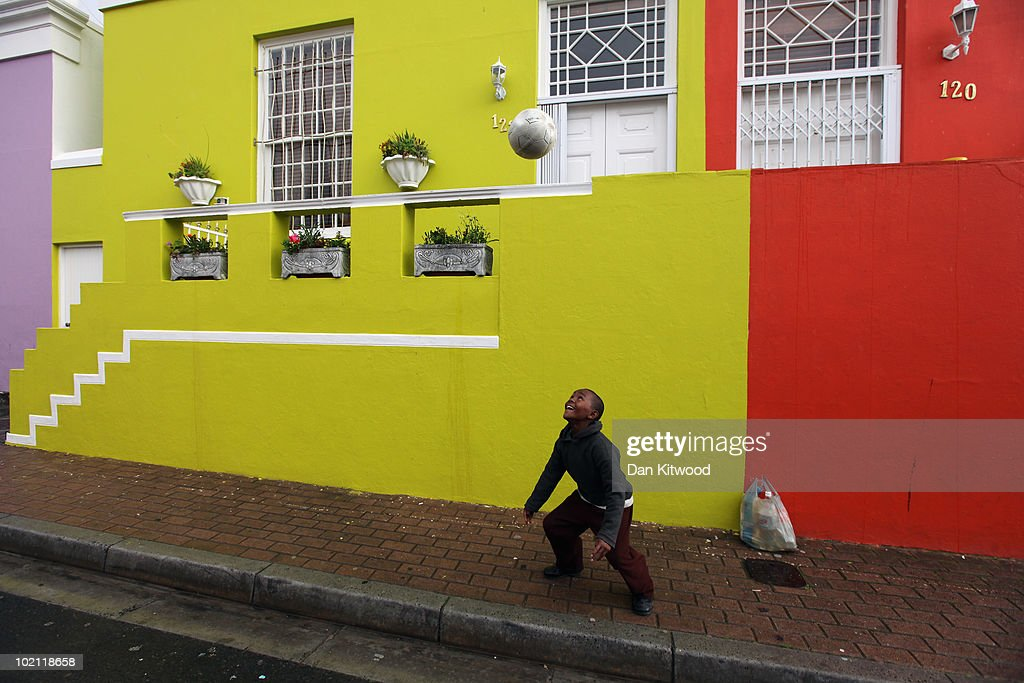 A boy Kicks a football down a street in the Bo Kaap area of Cape Town on June 15, 2010 in Cape Town, South Africa. The excitement and passion of the South African people for the for the World Cup has increased following a draw in the opening match between South Africa and Mexico on June 11, with thousands joining the official Bafana Bafana fan club, but for many ordinary South Africans the tickets to the games remain unaffordable. The final is scheduled to be played on July 11.