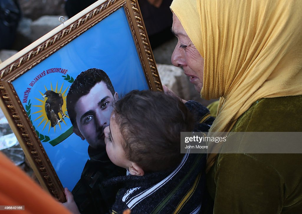 A boy kisses a photo of his father at a martyrs' cemetery for soldiers from the People's Protection Units (YPG), killed fighting ISIL on November 12, 2015 in Qamishli, Rojava, Syria. The predominantly Kurdish regions of northern Syria and Iraq have become bastions against the Islamic State, with the help of U.S. airstrikes. In Iraq, Kurdish Peshmerga forces launched an offensive to drive the extremists from Sinjar, which they had captured in 2014, killing and enslaving thousands of minority Yazidis.