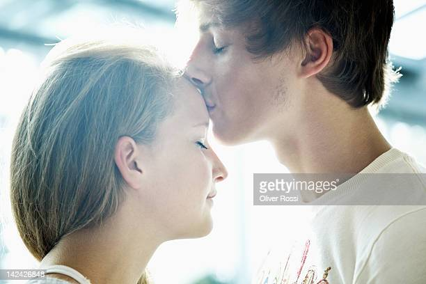 boy kisses forehead of his girlfriend