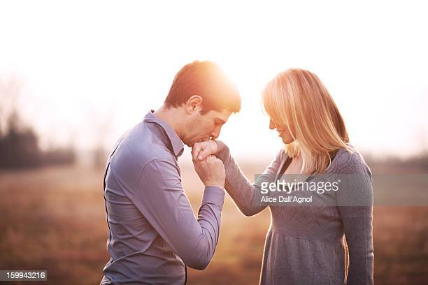 A boy kisses the hand of his girlfriend