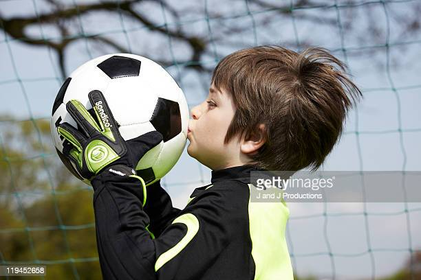 Boy kissing a football