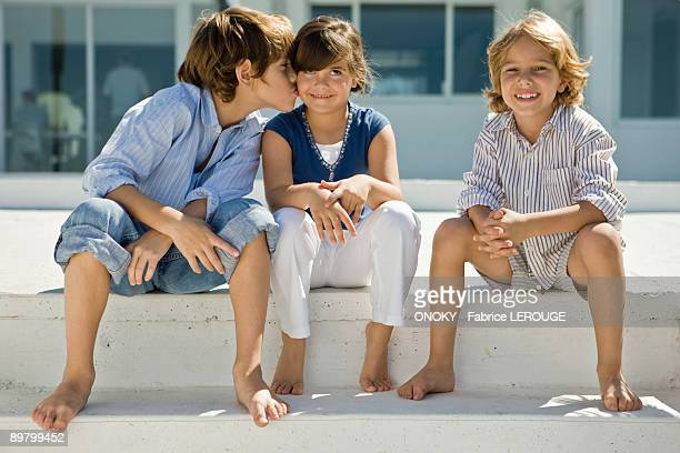Boy kissing a girl with his friend sitting beside them