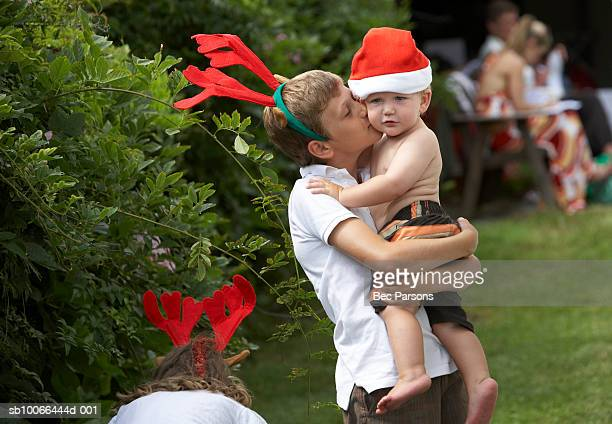 Boy (12-13) kissing brother (16-18 months) on lawn, with Christmas hats
