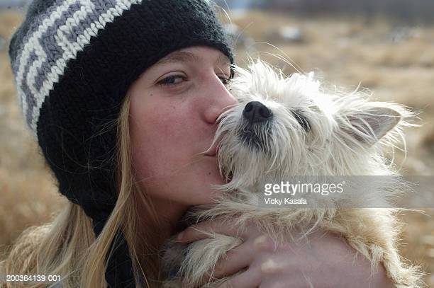 Boy (10-12) kissing dog on snout, portrait