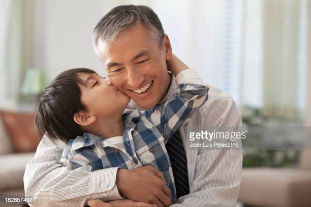 Boy kissing father's cheek