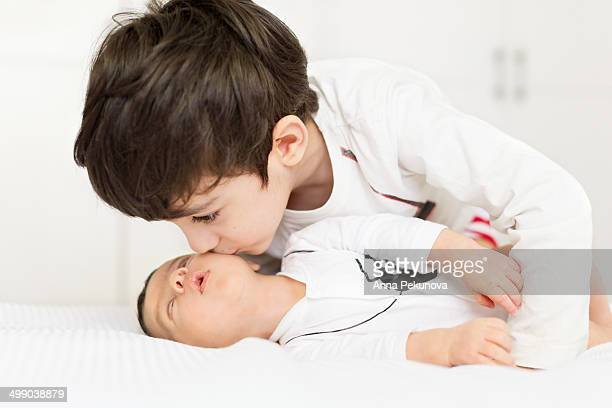boy kissing his baby brother - eastern european descent stock pictures, royalty-free photos & images