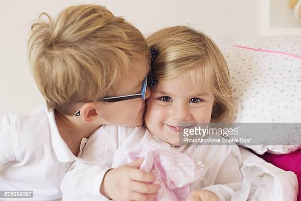 Boy kissing little sisters cheek