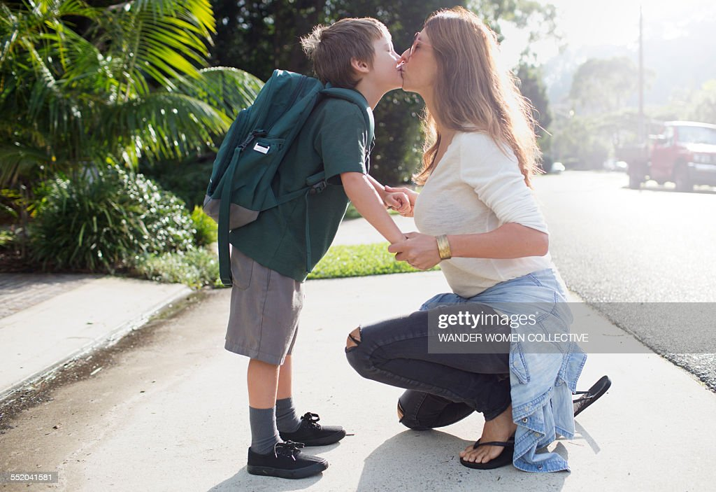 Boy kissing mother goodbye walking to school : Stock-Foto