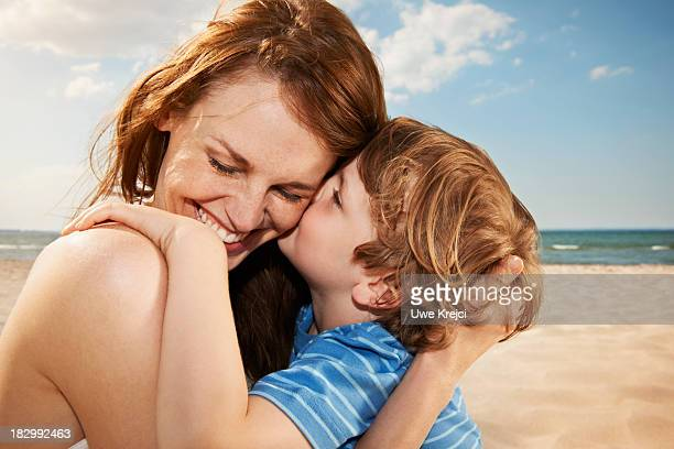 boy (4-5 years) kissing mother, smiling, close up - 4 5 years photos stock pictures, royalty-free photos & images