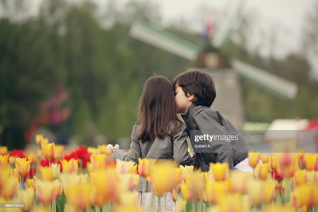 Boy kissing sister on cheek surrounded by tulips. : Stock Photo