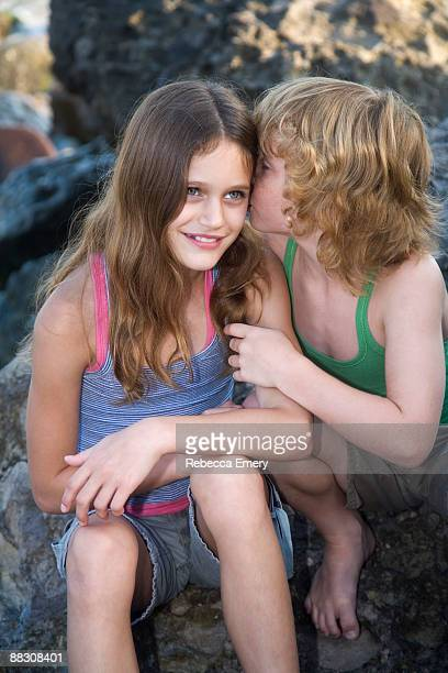 boy kissing smiling girl - emery stock photos and pictures