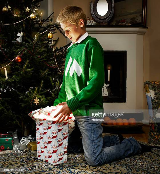 Boy (12-14) kneeling beside Christmas tree unwrapping present