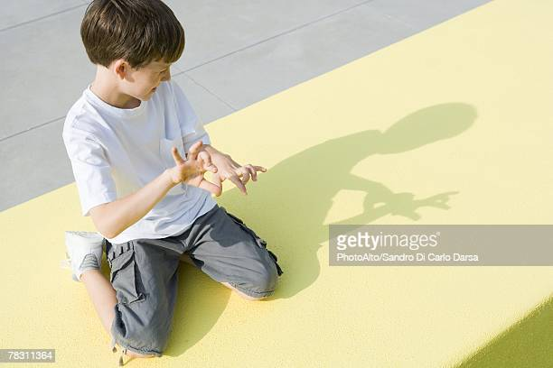 Boy kneeling on the ground, making shadow figures with hands, high angle view
