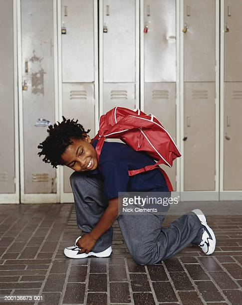 Boy (8-10) kneeling, tying shoelace, smiling, lockers in background