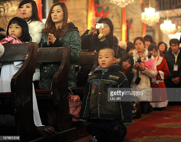 Boy kneels to pray during the Christmas Eve mass at a Catholic church in Beijing on December 24, 2010. The Vatican and China have not had formal...