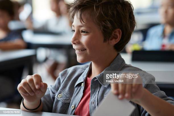 Boy laughing and holding paper note, sitting in classroom