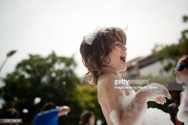 boy laughing at a foam party - bebe desnudo fotografías e imágenes de stock