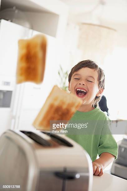 Boy laughing at toast popping out of toaster