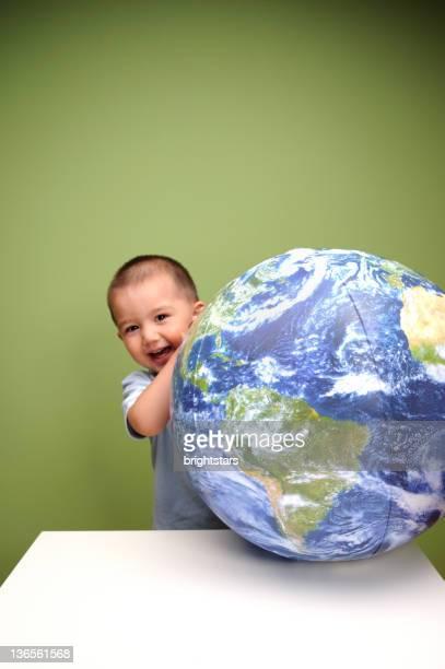 Boy laughing behind earth ball