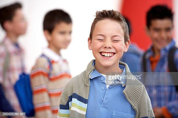 Boy (8-10) laughing, eyes closed, close-up