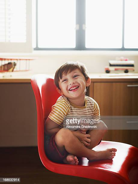 Boy Laughing in Red Chair