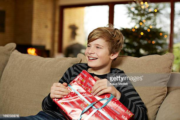 Boy laughing in sofa holding present