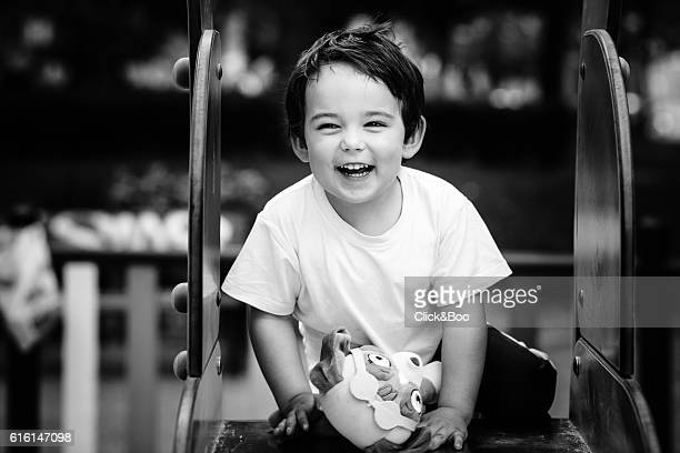 Boy laughing on the top of a slide
