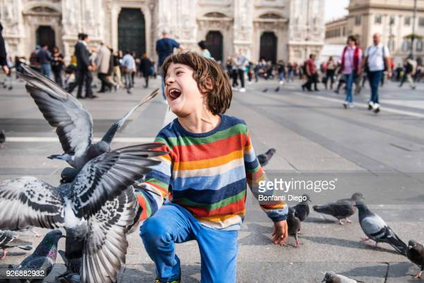 boy laughing while feeding pigeons in square, milan, lombardy, italy - cathedral stock pictures, royalty-free photos & images