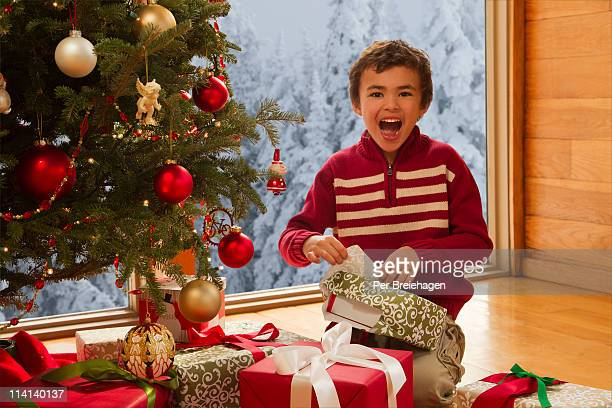 Boy laughing while opening christmas gift