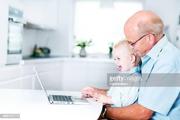 Junge lachen und spielen mit laptop-computer mit Opa