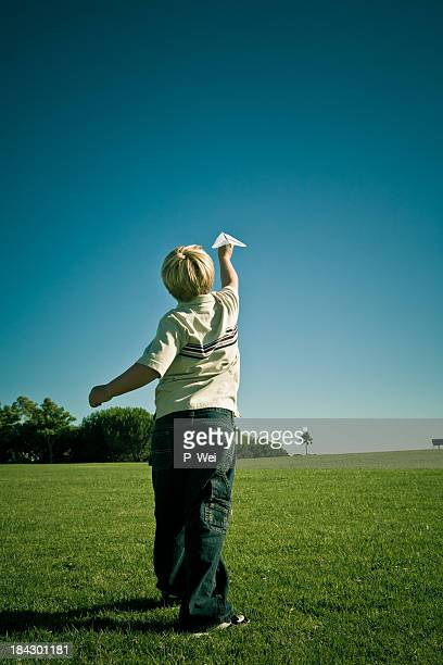 Boy launching a paper airplane.