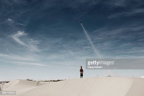 Boy launching model hobby rocket in desert