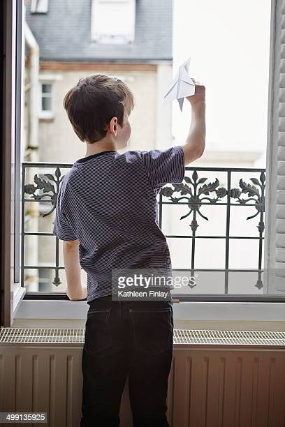 Boy launching paper plane from window