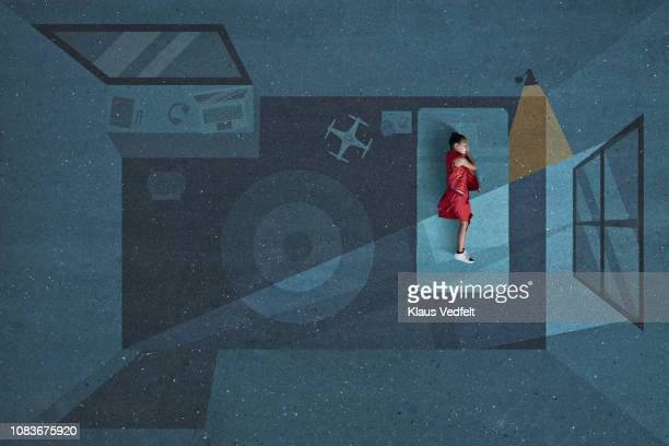 Boy laying and sleeping inside painted imaginary bedroom