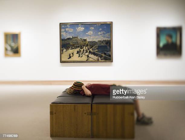 boy laying down on bench in art gallery with hat covering face - bokeh museum stock photos and pictures