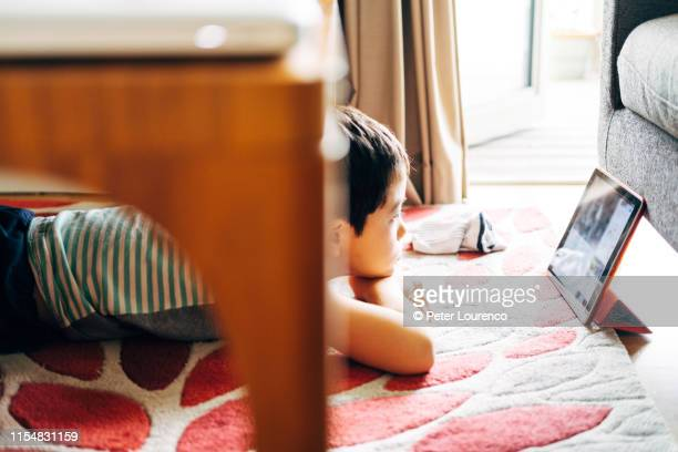 boy laying down watching tablet computer - peter lourenco ストックフォトと画像