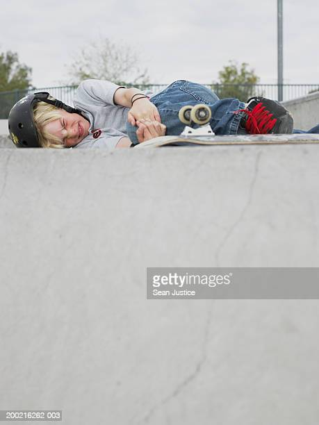 Boy (10-12) laying on ground with skateboard, holding knee