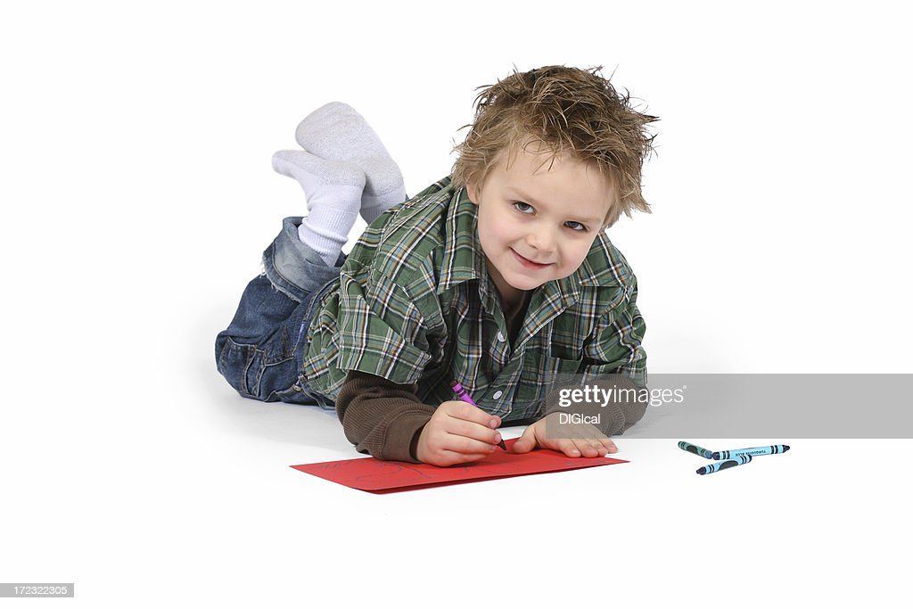Boy Laying On His Stomach Coloring With Crayons Stock Photo