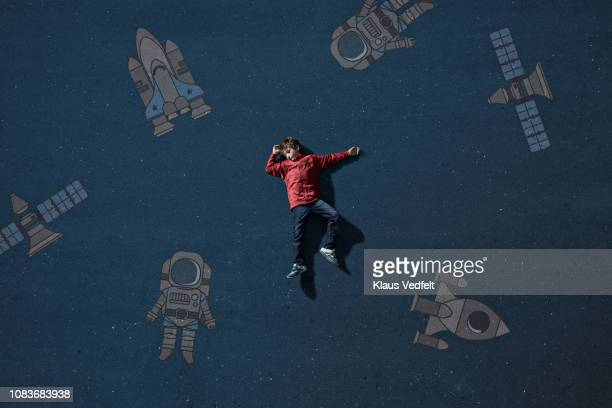 Boy laying on painted imaginary background among space travel objects