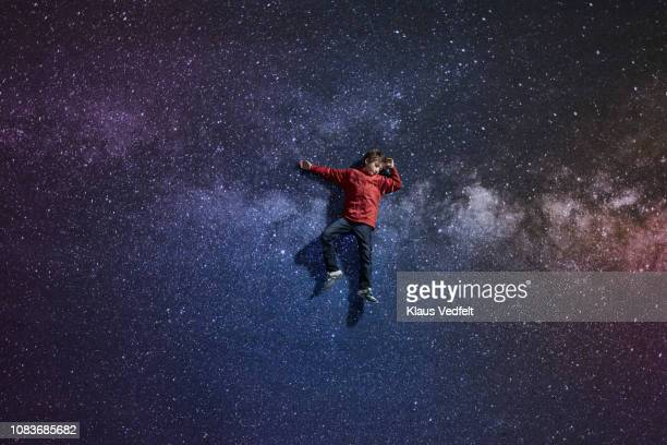 Boy laying on painted imaginary background of space with stars
